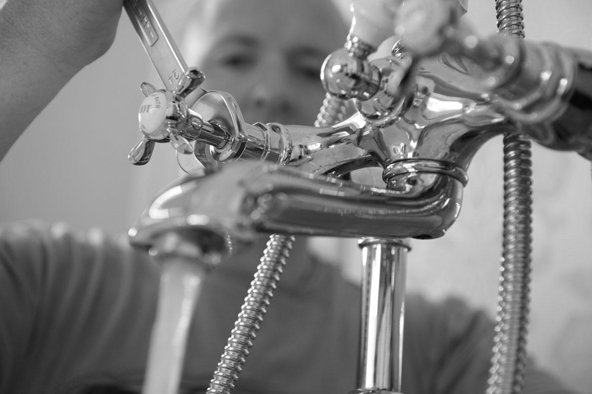 Rørlegger reparerer kran